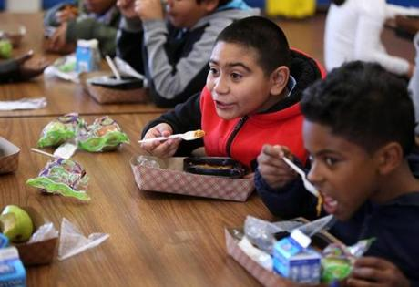 Boston, MA--10/21/2015--Fourth graders, including Jorge Peña (cq), 10, second from right, and Henry Hernandez (cq), 10, eat. School lunches, that were prepared in New York and trucked to Boston, are heated and served at the Blackstone Elementary School/Blackstone Innovation School, on Wednesday, October 21, 2015. Without a true cooking kitchen/cafeteria, the school's lunch area is called a satellite. Photo by Pat Greenhouse/Globe Staff Topic: schoolfood Reporter: James Vaznis