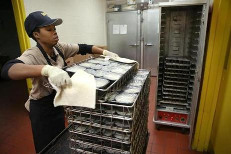 Boston, MA--10/21/2015--Satellite attendant Rachel Pierre (cq) moves 199 lunches (minus the one used for temperature testing) from the oven to this warmer. School lunches, that were prepared in New York and trucked to Boston, are heated and served at the Blackstone Elementary School/Blackstone Innovation School, on Wednesday, October 21, 2015. Without a true cooking kitchen/cafeteria, the school's lunch area is called a satellite. Photo by Pat Greenhouse/Globe Staff Topic: schoolfood Reporter: James Vaznis