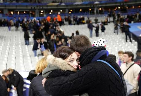 Two people on the pitch of the Stade de France stadium embraced.