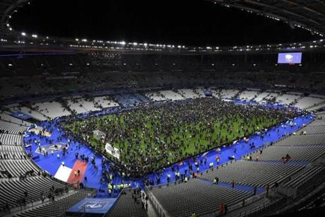 Spectators gathered on the pitch of the Stade de France following the friendly football match between France and Germany in Saint-Denis, north of Paris, after explosions were reported outside the national stadium.