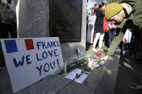 A man placed a candle at a makeshift memorial for those killed or wounded in the Friday attacks in Paris.