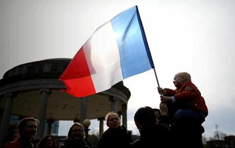 A boy held a French flag as people participated in a rally in Boston.
