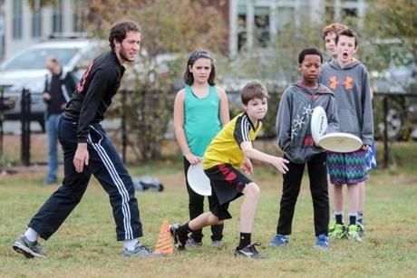Jonathan Malloy  (left) leads an Ultimate Frisbee clinic at Diamond Fields in Lexington.