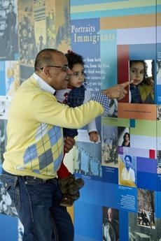 Skywalk Observatory Dreams of Freedom: Boston�s Immigrant Experience. Pictured: A Father showing his daughter the faces of a young Immigrant family. (handout)