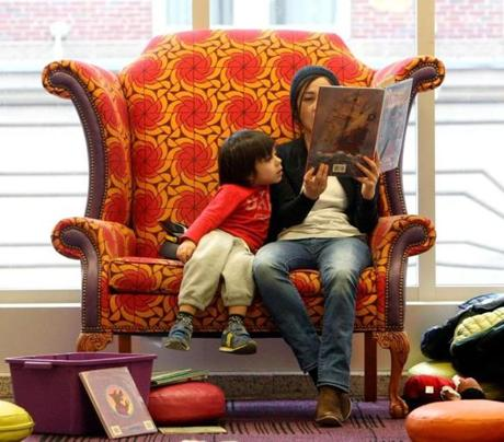 Boston, MA: 01-26-2016: Max Tovar (age 4) listens as his mother Connie Tovar reads in the Children's Library at the Boston Public Library in Boston, Mass. January 26, 2016. The area opened in February 2015 as part of phase one of an ongoing renovation project. Max's brother Bruno (age 1) had wandered off to explore. Photo/John Blanding, Boston Globe staff story/Dan Adams, Business ( 15BPLrenovations )