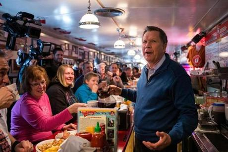 Republican presidential candidate Ohio Governor John Kasich served coffee to patrons at the Red arrow Diner in Manchester, N.H.