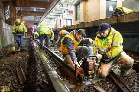 Rick Keefe (left) assisted Matty Crowell with a rail drill as workers repaired rails at JFK/UMass station.