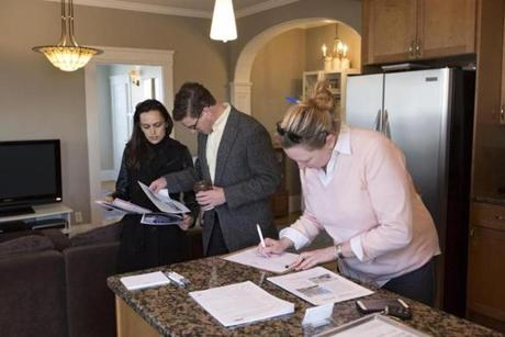 Maria Arabatzis (left) and Brian Egan, potential first-time home buyers, looked over marketing materials during an open house of a one-bedroom condo in Jones Hill in Dorchester.