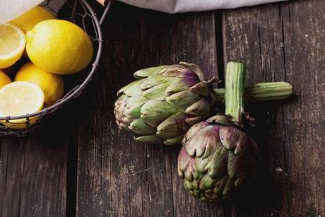 Ripe Organic Artichokes on the rustic wooden board with lemon, napkin ...