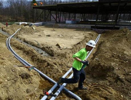 An electrical worker crossed a ditch with tubing at the Devens construction site.