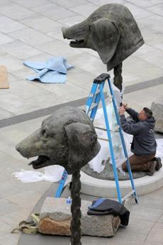 A worker installed artist Ai Wei Wei's Chinese zodiac sculptures on the Rose Kennedy Greenway near Milk Street.
