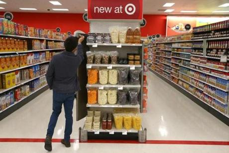 Seijen Takamura, a Target employee, checked specially packaged food items on a new-product display shelf in the store.
