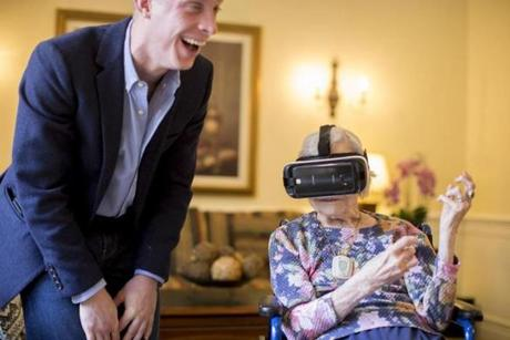 Doris Nakashian, 93, a senior at the Orchard Hill assisted living facility in Sudbury, was transported to various places in a virtual reality demonstration with the assistance of Dennis Lally (left).