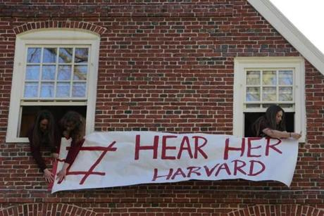 Protesters hung a banner outside Massachusetts Hall before a rally and march around Harvard Yard.
