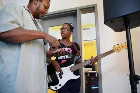 Boston police detective Jeremiah Benton (left) helps Kamiylah Parks, 13, of Dorchester, with bass guitar fingerings.