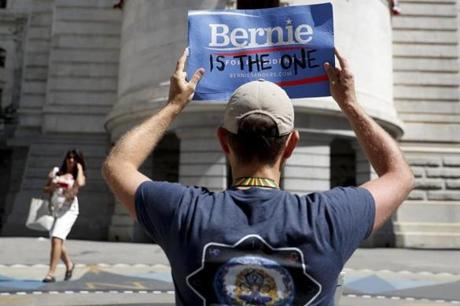 A supporter of Sen. Bernie Sanders, I-Vt., holds up a protest sign in Philadelphia, Tuesday, July 26, 2016, during the second day of the Democratic National Convention. (AP Photo/John Minchillo)