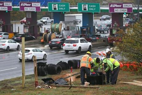 Construction workers alongside the Pike prepared on Friday to begin demolition of the soon-to-close tollbooths.