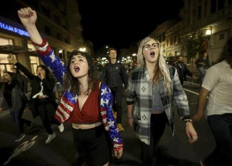 Madeline Lopes (left) and Cassidy Irwin, both of Oakland, Calif., marched with other protesters following Donald Trump's election victory.
