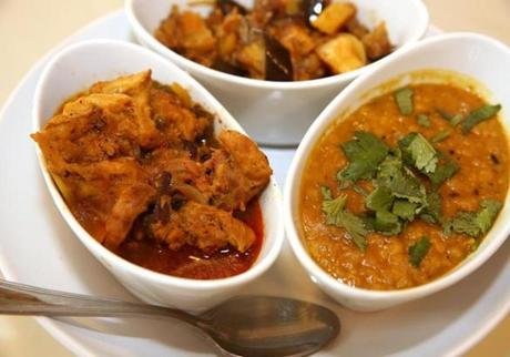 Clockwise from left: Kukul mas (chicken) curry, eggplant and potato curry, parippu (lentils).