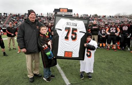Woburn, MA: 11-24-2016: Retiring Woburn High School coach Rocky Nelson with his grandsons Dylan Sigsbury (left) and Quinn Boyd during ceremonies before start of Thanksgiving Day football game against Winchester HS at Woburn HS in Woburn, MA Nov. 24, 2016. Photo/John Blanding, Boston Globe staff story/, Sports (25woburn)