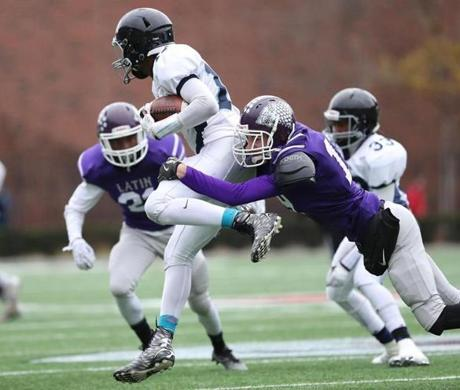 Cambridge MA 11/24/16 Boston English quarterback Shaquille Wharwood is tackled by Boston Latin James Hickey during first quarter action of their Thanksgiving Day football game at Harvard Stadium. (Photo by Matthew J. Lee/Globe staff) topic: 25bchigh reporter: