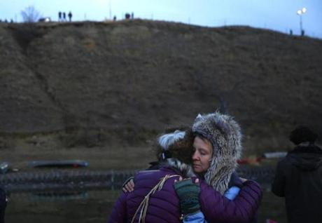 Protesters embraced as police stood on a hilltop in Cannon Ball, N.D. near Standing Rock.