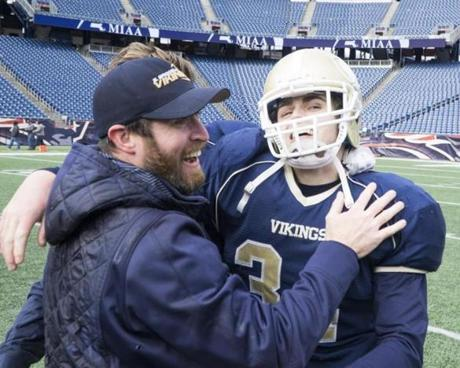 8.3.862095736_Sports_04d3abowl After winning the game, East Bridgwater's head coach Shawn Tarpey celebrates with senior running back Patrick Snow (34) during the division 3a game at Gillette Stadium in Foxborough, Mass., Saturday Dec. 3, 2016. East Bridgewater defeated St. Marys of Lynn 34-8 to capture the title. (Robert E. Klein for the Boston Globe)