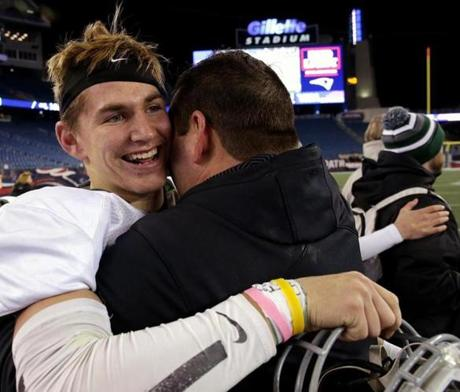Foxborough, MA - 12/03/2016 - Duxbury Dragons quarterback Bobby Maimaron (10) and his father Duxbury Dragons head coach David Maimaron share an embrace as time runs out in the D2 Super bowl. MIAA Super Bowls: Division 2 Shrewsbury vs. Duxbury at Gillette Stadium in Foxborough. - (Barry Chin/Globe Staff), Section: Sports, Reporter: Trevor Hass, Topic: 04HS Super Bowls, LOID: 8.3.862095835.