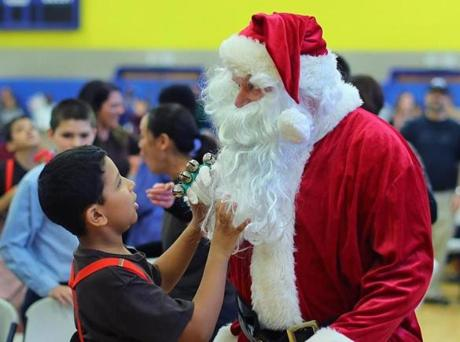 Randolph-12/22/16 The Boston Higashi School held their annual Winter Music Festival. Student Adam Garchali, 9, checks out Santa's beard. The school has a unquie approach to teaching children with autism incorporating arts and music into their programs. John Tlumacki/Boston Globe(metro)