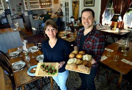 Plymouth 12/30/2016 : Owner of the Farmer's Table in Plymouth, Lynn Tripp holds Gorgonzola-stuffed dates and Marty Brent (right) holds a tray of muffins, scones and cookies. Photo by Debee Tlumacki for the Boston Globe (regional)