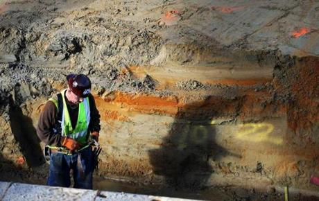 A construction worker was deep in a mud pit along with his shadow at the Pier 4 consturction site.