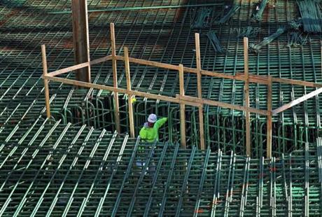 A worker stood below steel reinforcement bars at Pier 4, where Tishman Speyer is developing two buildings, one office and one luxury condos.