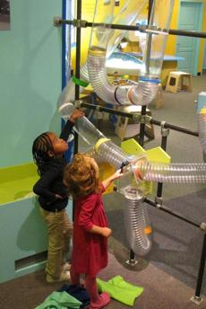 Ciara Cullina and Paloma Lombardi-Ortiz (both age 5) of Providence send balls and scarves flying through giant air tubes in Play Power, the newest exhibit at Providence Children's Museum.