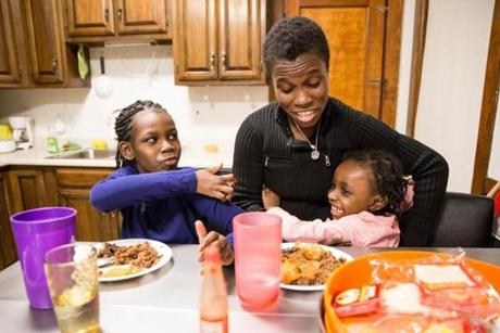 02/16/2017 ROSLINDALE, MA Sandy Guerrier (cq) (center) plays with her children Imanie (cq) (left) and Ammattieia (cq) during dinner at their home in Roslindale. (Aram Boghosian for The Boston Globe)