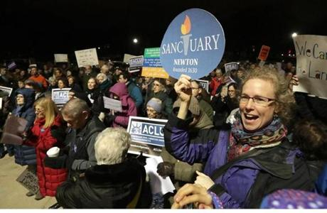 "Newton, MA: 02-21-2017: Julie Crosson (with sanctuary sign) was among the crowd at a rally calling for the city council make Newton a ""Welcoming City,"" outside Newton City Hall in Newton, Mass. Feb. 21, 2017. Photo/John Blanding, Boston Globe staff storyFelicia Gans, Metro ( 22newton )"