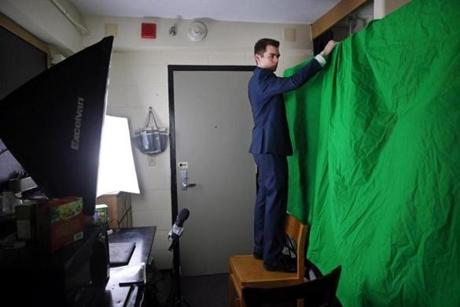Nicholas Fuentes hung a green screen while preparing to shoot his show in a friend's dorm room.