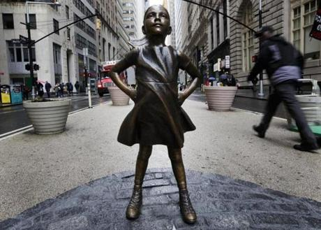 People are seen around a sculpture titled 'The Fearless Girl' by artist Kristen Visbal which was installed overnight facing the famous sculpture of the charging bull in Lower Manhattan by State Street Global Advisors.
