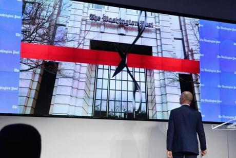 "WASHINGTON, DC - JANUARY 28: Amazon founder and Washington Post owner Jeff Bezos conducts a ""digital ribbon cutting"" during the opening ceremony of the newspaper's new location January 28, 2016 in Washington, DC. Bezos purchased the newspaper and media company in October of 2013 from the storied Graham family. (Photo by Chip Somodevilla/Getty Images)"