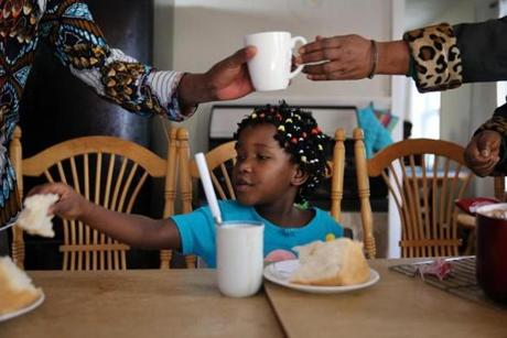 Seven-year-old Sarah Bayavuge (above) sat at the table in her family's home in Lowell.