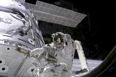 STS-88 mission specialist James Newman, holding on to a handrail, waves back at the camera during the first of three Extravehicular activities(EVAs) performed during the mission. The orbiter can be seen reflected in his visor
