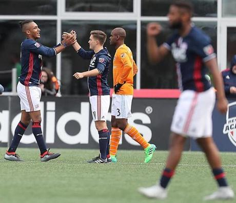 Juan Agudelo (left) celebrates his goal with teammmate Kelyn Rowe as Houston's Adolfo Machado walks by during second half action of the Revolution's 2-0 victory Saturday in Foxborough.