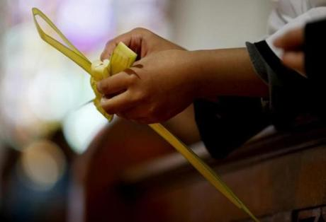 A parishioner held a palm during Palm Sunday mass at St. Rose of Lima church.