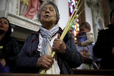 A parishioner helds a palm as she prays during Palm Sunday mass at St. Rose of Lima church.
