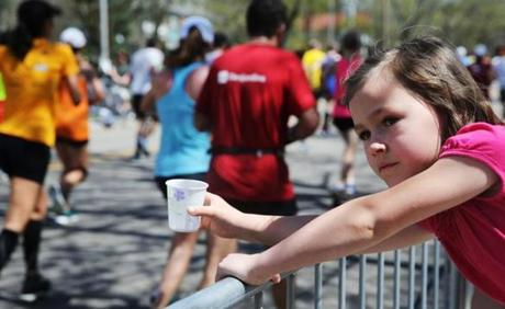 Ella Eaton, 6, offered water to runners in Newton.