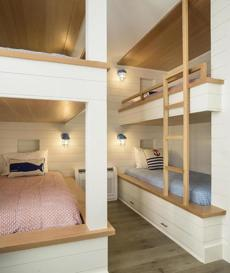 "In the bunk room, where young cousins sleep during ""family week"" in summer, the ceiling detail and trim are also edge-grain fir with a clear finish. Lantern-style sconces, no-nonsense ladders, and under-bed storage build on the nautical theme."