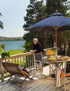 Annika Richter on the deck overlooking Scargo Lake. The teak table and chairs are by  Kingsley Bate.