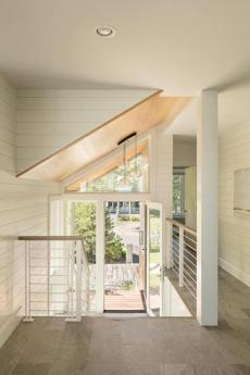 Seamlessly connecting outside and inside in the front entry, an edge-grain fir ceiling joins walls lined with crisp nickel-gap siding painted Benjamin Moore White Dove, lending a subtle texture and nautical feel to the space. The rails are powder-coated steel topped with white oak stained to match the floor.