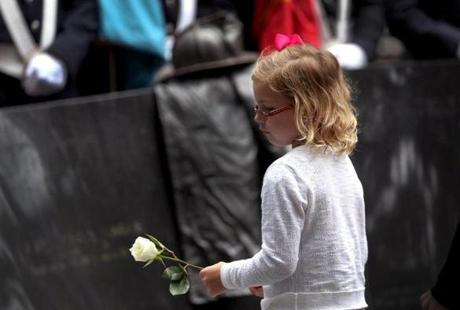 Abby Sweeney, 6, placed a rose on the memorial for the nine firefighters who died in the Hotel Vendome fire.