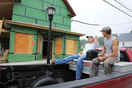 Electricians Jonathan Jandreau (left) and Seth Flanders took a break in the back of a pickup truck outside the Monson General Store.