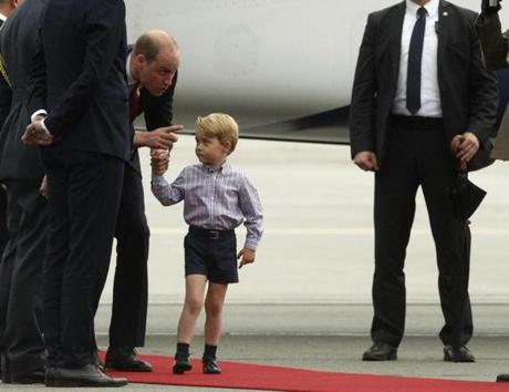 Britain's Prince William held his son's hand Prince George in Poland Monday.